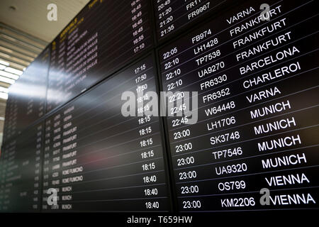 Boarding time monitor screens - timetable boards. Arrivals and departures monitors to check the status of a flight on the airport. Vienna, Munich, Cha - Stock Photo