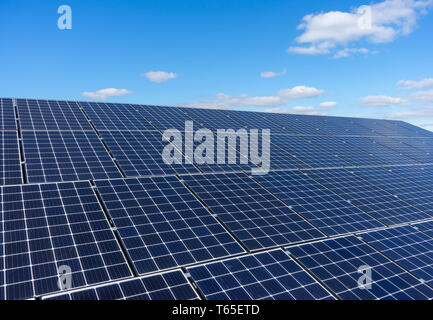Solar panels on a roof with a blue sky and white clouds background - Stock Photo