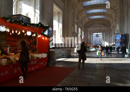 Milan/Italy - January 15, 2014: Traditional Italian Christmas market stalls decorated with the red fabric and red carpet inside the Central station. - Stock Photo