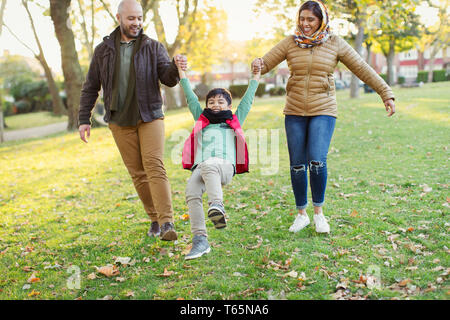 Playful Muslim family in autumn park - Stock Photo