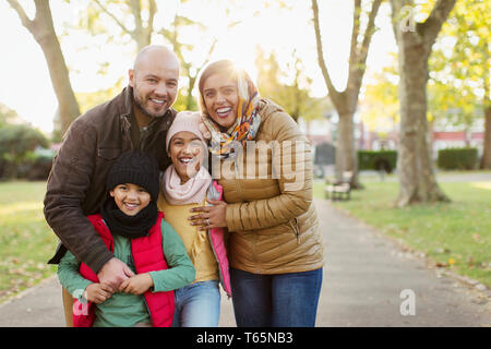Portrait happy Muslim family in autumn park - Stock Photo
