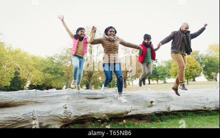 Happy, playful family holding hands, jumping off log in autumn park - Stock Photo