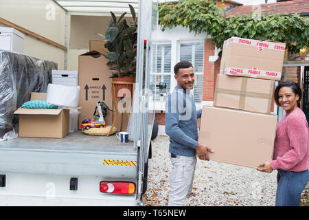 Portrait happy couple moving house, unloading cardboard boxes from moving van - Stock Photo