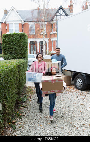 Family moving into new house, carrying  belongings from moving van in driveway - Stock Photo
