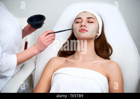 Beautician at work. Hands of cosmetology specialist applying facial mask using brush, making skin hydrated and healthy. Attractive woman relaxing with - Stock Photo