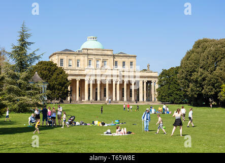 Cheltenham Pittville Pump Room with people having a picnic and children playing Pittville Park, Cheltenham Spa Gloucestershire, England, UK,GB, Europe - Stock Photo