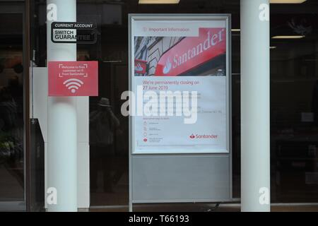A notice informing customers of the closure of the Santander Bank in Buxton, Derbyshire. - Stock Photo