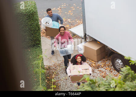 Family moving into new house, carrying boxes from moving van - Stock Photo