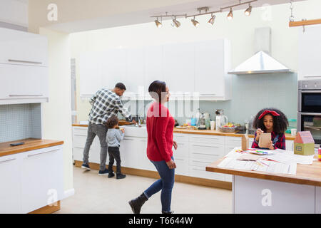 Family doing dishes and making crafts in kitchen - Stock Photo