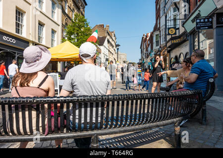 People sit on benched in Peascod Street in Windsor. Benches are also security measure forming ant-vehicle barriers. - Stock Photo