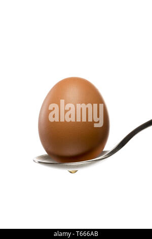 brown egg on a spoon, isolated on white - Stock Photo