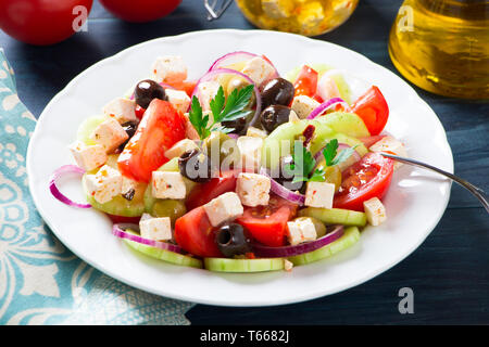 Fresh greek salad with tomato, cucumber, purple onion, feta cheese and olives on a blue wooden table - Stock Photo