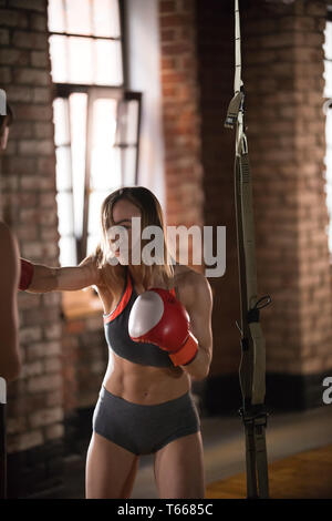An aggressive woman boxer hitting the punching bag in the gym - Stock Photo