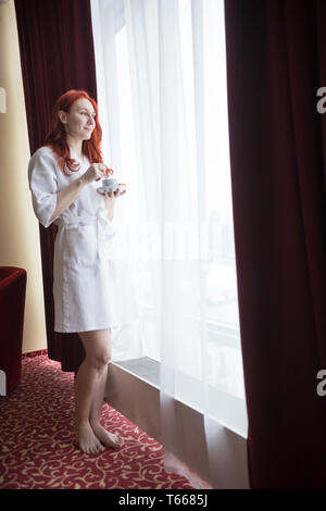 A ginger woman standing by the window and holding a cup of coffee - Stock Photo