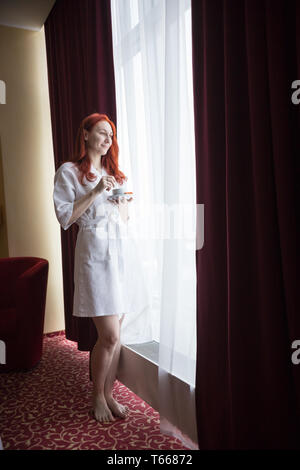 A ginger woman standing by the window and looking at the streets - Stock Photo