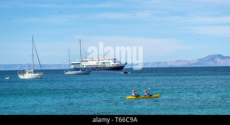 A couple paddle a yellow kayak with sailboats and the National Geographic Venture cruise ship in the background off shore of Isla San Francisco, Baja  - Stock Photo