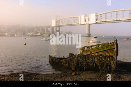 Royal Albert bridge over the river Tamar and rotten, abandoned boat on river bank at dawn in Plymouth, Devon, UK. - Stock Photo