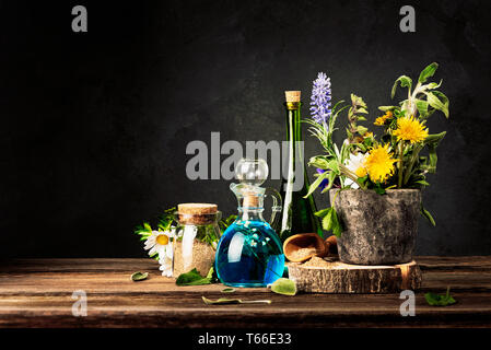 Homeopathy and Alternative Medicine. Healing Herbs in stone mortar and Essential Oil in Glass Bottles. Crushed healing herbs on wooden table. - Stock Photo
