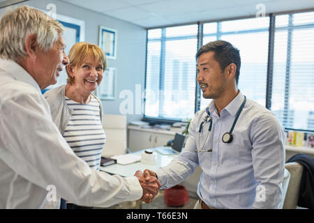 Male doctor shaking hands with senior couple in clinic doctors office - Stock Photo