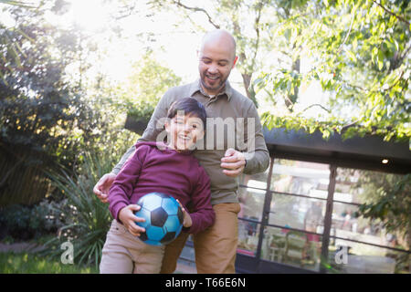 Father and son playing with soccer ball in backyard - Stock Photo