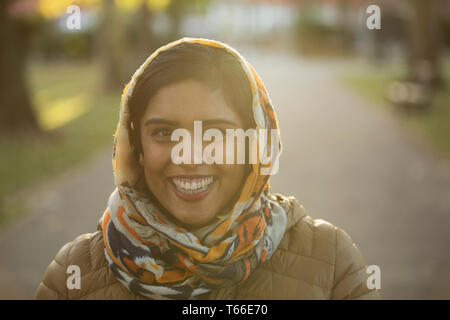Portrait smiling, confident Muslim woman wearing hijab in park - Stock Photo