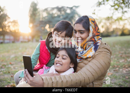 Muslim mother in hijab taking selfie with camera phone in autumn park - Stock Photo