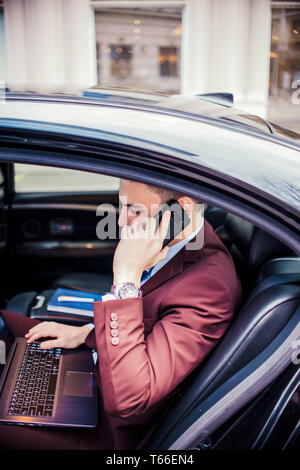 Elegant businessman is sitting in his limo car with opened door and talking on mobile - Stock Photo