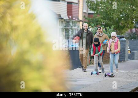 Muslim family walking and riding scooters on neighborhood sidewalk - Stock Photo