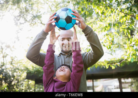 Father and son playing soccer in sunny park - Stock Photo