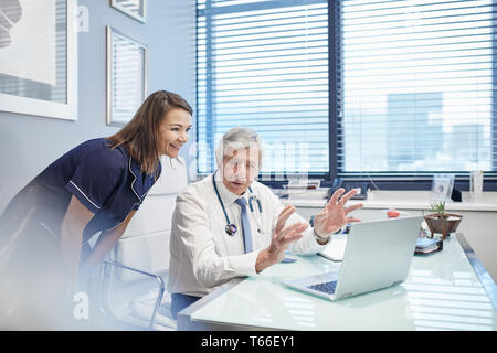 Doctor and nurse talking at laptop in doctors office - Stock Photo
