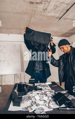 Robbers are holding empty bag with the stolen money near them - Stock Photo