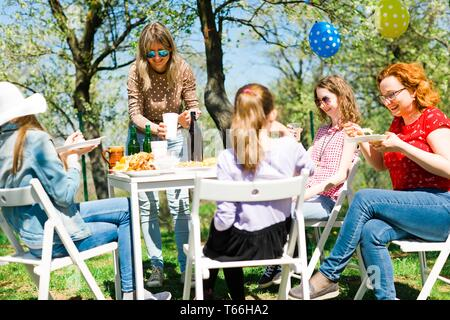 Birthday garden party during summer sunny day - eating on picnic - Stock Photo