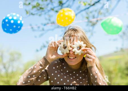 Woman making fun - glasses from home made cakes - summer garden party - Stock Photo