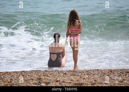 Two young girls in bathing suits, on seaside beach, looking out onto blue sea and white shore waves - Stock Photo