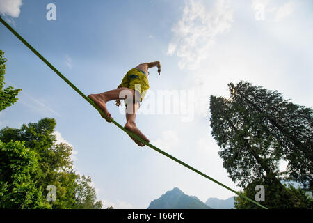 Sporty boy practices walking on the rope - Stock Photo