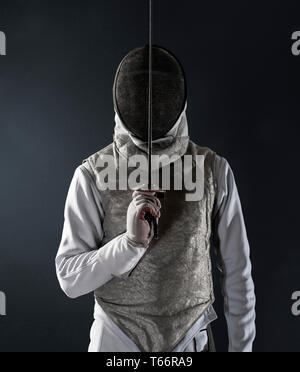 Portrait man in fencing uniform and mask - Stock Photo