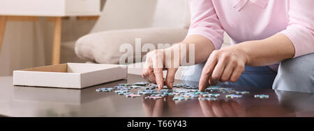 Elderly female hands trying to connect pieces of jigsaw puzzle. Creative idea for Alzheimer's disease, dementia, memory loss and mental health concept - Stock Photo
