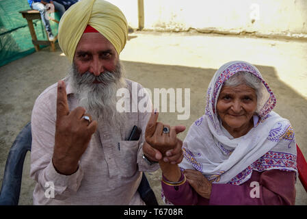 Kashmiri voters are seen showing off their inked fingers after casting their votes outside a polling station in Kulgam, South of Srinagar. On the fourth phase of India's Parliamentary elections, Indians went to polls to cast their ballots amid complete shutdown and internet gag. - Stock Photo