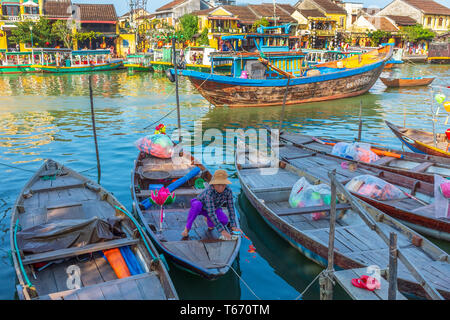Local Vietnamese fisher woman cleaning her fishing boat at the harbour on Son Thu Bon river at Hoi An in Quang Nam Provence, Vietnam, Asia - Stock Photo