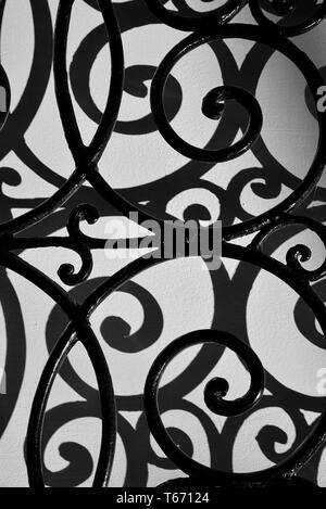Curved iron bars casting shadows on wall. - Stock Photo