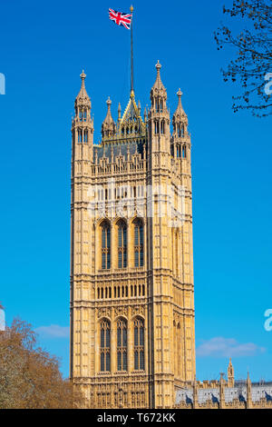 London, England – April 10, 2019: The Union Jack flag flying from the roof of  the Victoria tower at the southern end of the Houses of Parliament - Stock Photo
