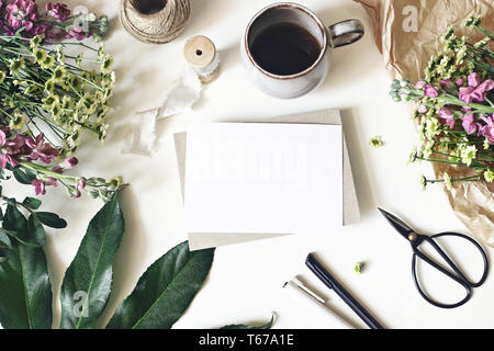 Floral lifestyle, stationery scene. Mums, matthiola flowers, aralia leaf, cup of coffee and vintage scissors on white table. Blank greeting card - Stock Photo