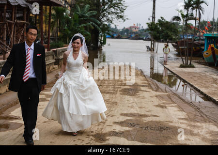 Newly wed Vietnamese couple married in western style clothing walking away from restaurant on waterfront - Stock Photo