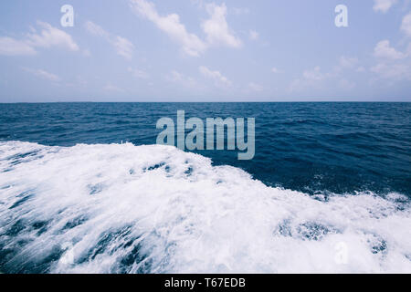 blue water background with ripples. Close up Nature background. Soft focus with selective focus. Waves behind a boat on a calm sea. - Stock Photo