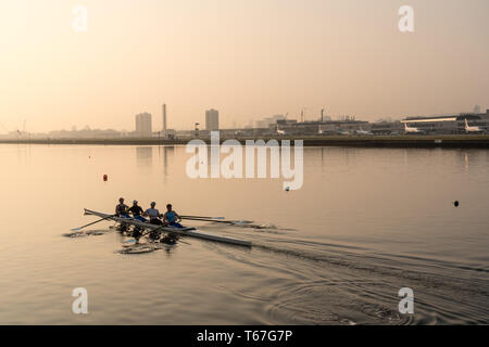 Rowers by London City Airport at sunrise on misty day - Stock Photo