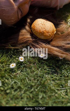 Successful business woman lying on grass with fast food burger cheesburger on hair enjoying leisure free time in a park with blossoming sakura cherry - Stock Photo