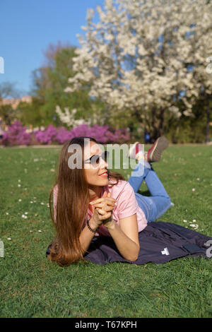 Successful business woman lying on grass enjoying leisure free time in a park with blossoming sakura cherry trees wearing pink t-shirt - Stock Photo