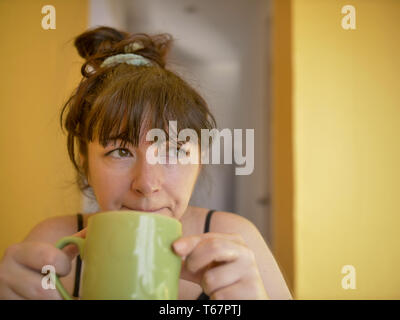 Sad and sleepy young attractive woman with a cup of coffee in the morning at home - Stock Photo