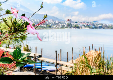 Hibiscus flowers in foreground with jetty, canoes & Lake Atitlan behind & town of Santiago Atitlan, Guatemala in background. - Stock Photo