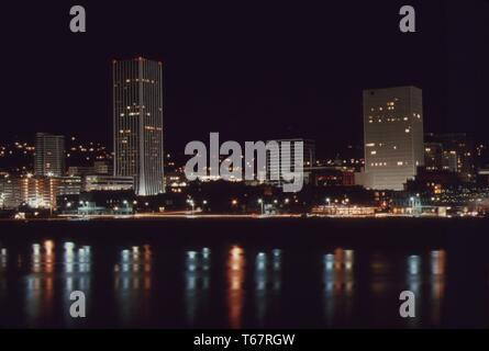 Downtown core area of Portland, after 7pm on November 2 1973, during the state's energy crisis with few commercial and neon lighting displays. This photo looks toward the west with the Willamette river in the foreground. Image courtesy National Archives, United States, November 2, 1973. - Stock Photo